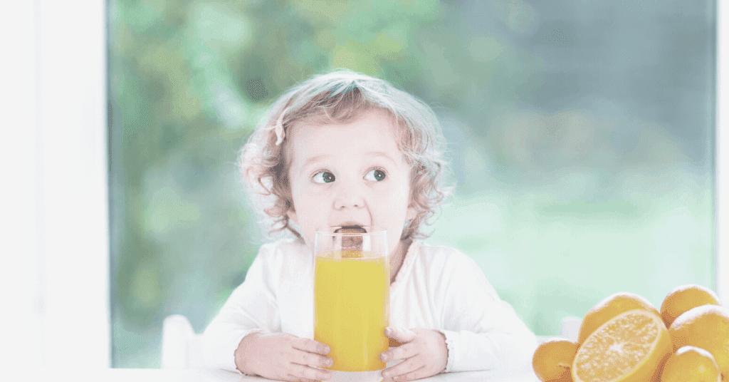 toddler drinking orange juice