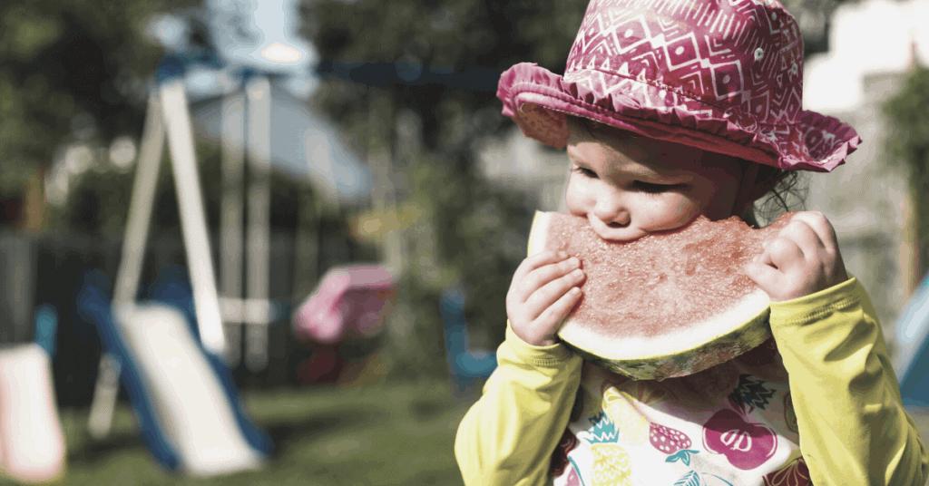 Toddler eating melon