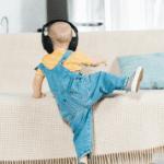Toddler wearing headphones climbing on chair